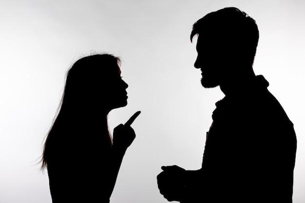 Agressie en misbruik concept. man en vrouw die huiselijk geweld uiten in studio silhouet