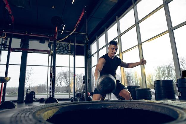 Agressief. jonge gespierde blanke atleet traint in de sportschool, doet krachtoefeningen, oefent, werkt aan zijn bovenlichaam