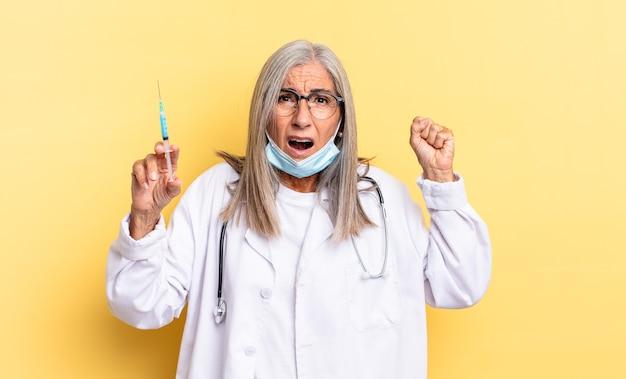 Agressief schreeuwen met een boze uitdrukking of met gebalde vuisten om succes te vieren. dokter en vaccin concept