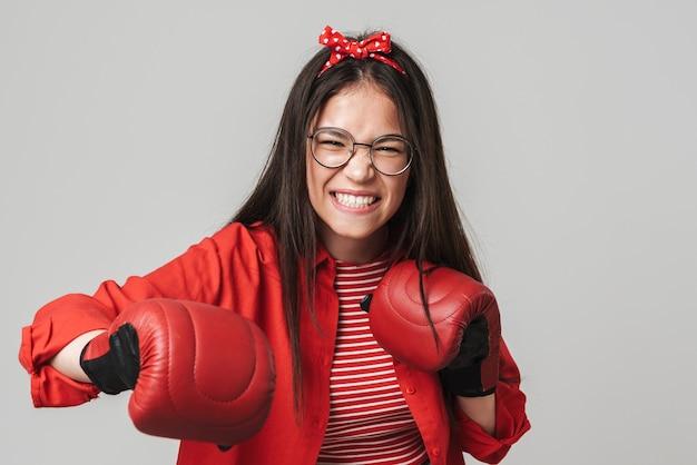 Agressief tienermeisje met een casual outfit die geïsoleerd staat over een grijze muur, bokshandschoenen draagt, boksen