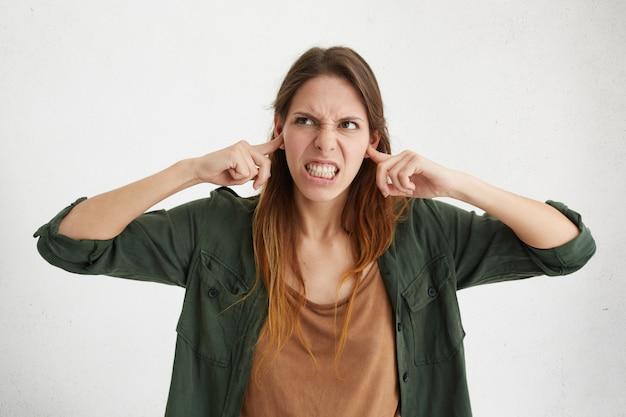 Agressief vrouwtje dat haar oren stopt die boos zijn op lawaai. geïrriteerde jonge vrouw die harde geluiden probeert te vermijden