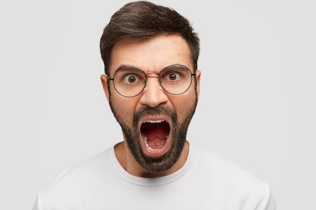 Agressieve aantrekkelijke man schreeuwt woedend, geïrriteerd door slechte service, maakt ruzie met directeur van het bedrijf