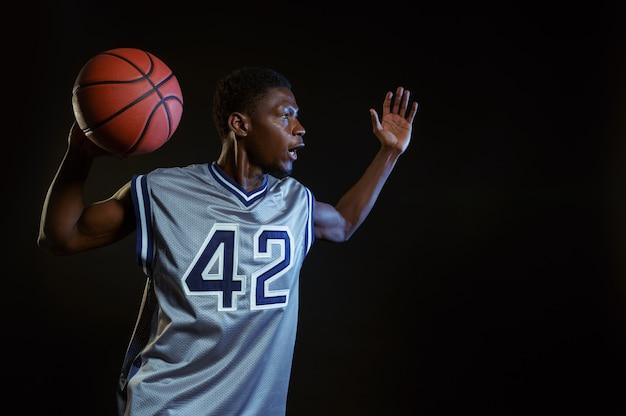 Agressieve basketbalspeler poseert met bal in studio, zwarte achtergrond. professionele mannelijke baller in sportkleding die sportspel speelt, lange sportman