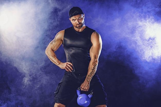 Agressieve bebaarde gespierde bodybuilder doet oefening voor de biceps met kettlebell.