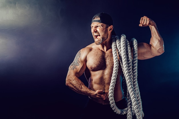 Agressieve bebaarde gespierde sportman die slagtouw op donkere muur met rook houdt. kracht en motivatie.