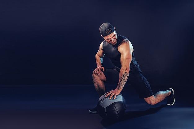 Agressieve bebaarde gespierde sportman traint met een medicijnbal geïsoleerd op donkere muur.