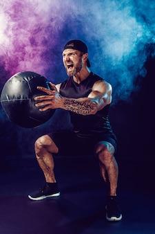 Agressieve bebaarde gespierde sportman traint, push-up met een medicijnbal geïsoleerd op donkere muur met rook.