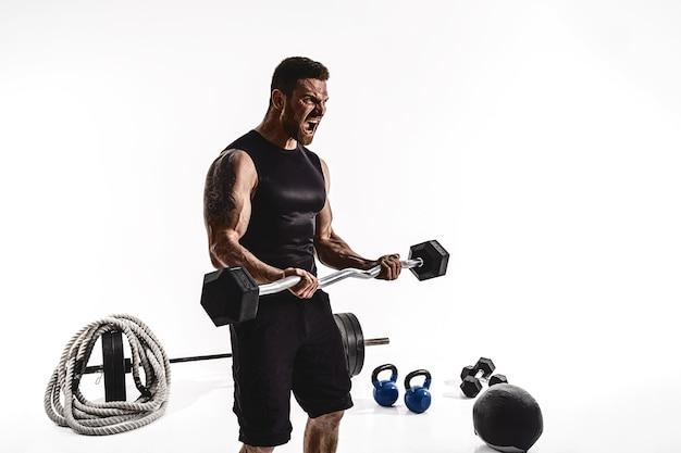 Agressieve bebaarde sterke gespierde man in sportkleding training op biceps met barbell op wit isoleren.