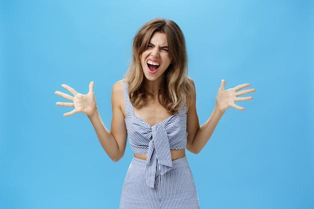 Agressieve beu vriendin met slordig haar en gapende tanden die schreeuwen, opgeheven handen zijwaarts schreeuwen, schreeuwen van woede en een hekel hebben aan ziek en moe van leugens die ruzie maken over blauwe muur. emoties concept Premium Foto
