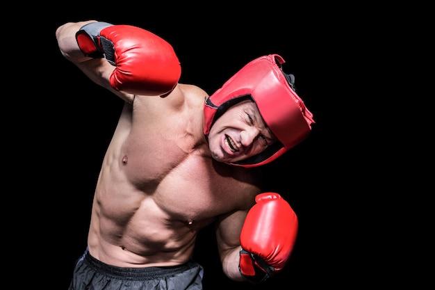 Agressieve bokser die tegen zwarte achtergrond puching