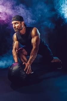 Agressieve brute bebaarde gespierde sportman traint met een medicijnbal geïsoleerd op donkere muur met rook.