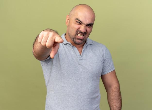 Agressieve, casual man van middelbare leeftijd die kijkt en wijst geïsoleerd op olijfgroene muur