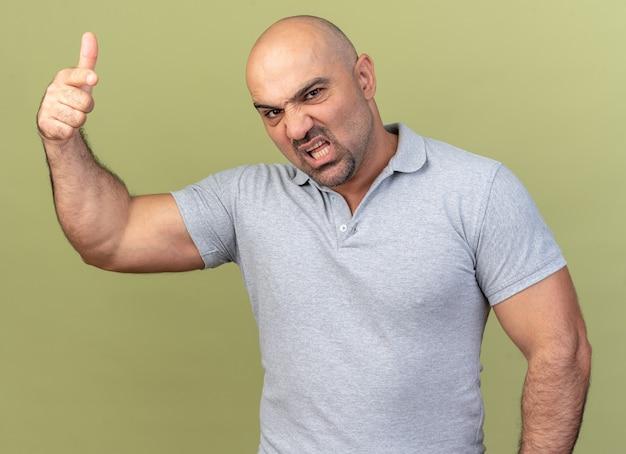 Agressieve, casual man van middelbare leeftijd die kijkt en wijst naar de voorkant geïsoleerd op olijfgroene muur
