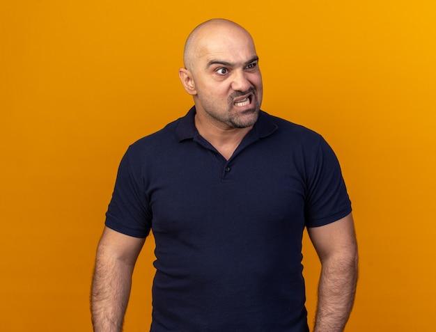 Agressieve casual man van middelbare leeftijd kijken naar kant geïsoleerd op oranje muur