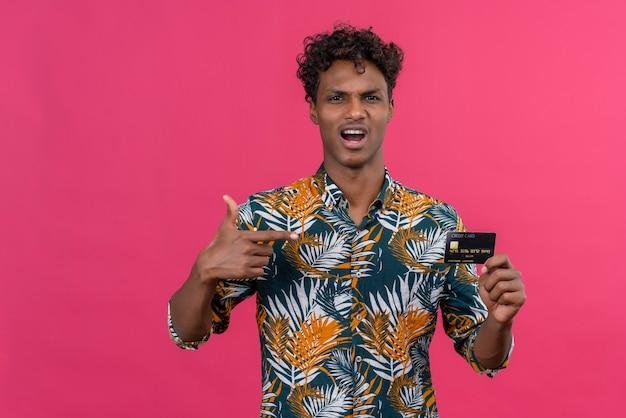 Agressieve en boze jonge donkere man met krullend haar in bladeren gedrukt overhemd wijzend op creditcard