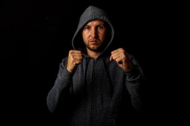 Agressieve jonge bebaarde man in een sweatshirt met een kap toont zijn vuisten op een zwarte achtergrond.