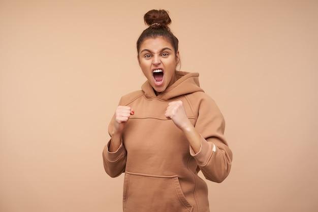 Agressieve jonge bruinharige vrouw gekleed in naakt sweatshirt die opgewonden schreeuwt terwijl ze naar de voorkant kijkt en haar handen opheft, geïsoleerd over beige muur