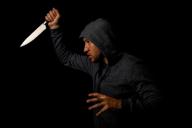Agressieve jonge man in een hoodie met een mes