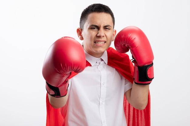 Agressieve jonge superheld jongen in rode cape doos handschoenen kijken camera houden hand in lucht uitrekken een andere richting camera geïsoleerd op witte achtergrond