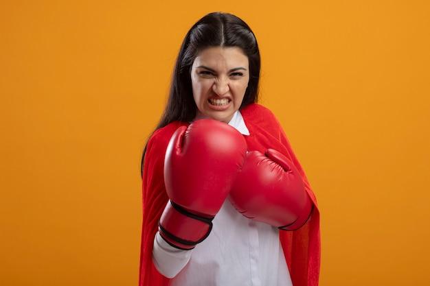 Agressieve jonge supervrouw die dooshandschoenen draagt die voorzijde bekijkt die boksgebaar doet dat op oranje muur wordt geïsoleerd