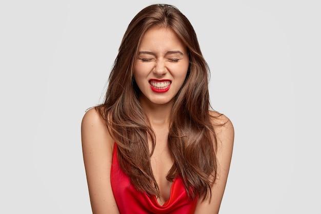 Agressieve jongedame klemt tanden met een geërgerde uitdrukking, houdt niet van iets