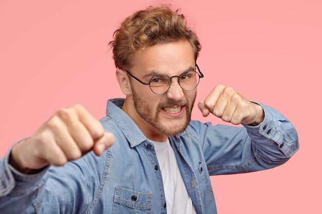 Agressieve man bijt met vuisten, heeft een boze uitdrukking, verdedigt zichzelf, klemt zijn tanden tegen woede