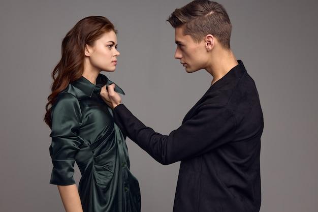 Agressieve man in een pak houdt een vrouw vast bij de kraag van een jurk op een grijze achtergrond. hoge kwaliteit foto