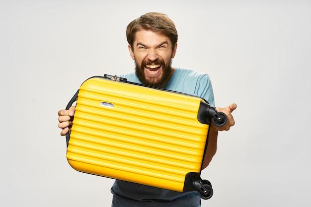 Agressieve man met gele koffer blauw shirt model lichte achtergrond