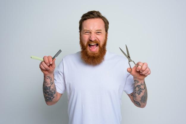 Agressieve man met schaar en mes is klaar om de baard te knippen