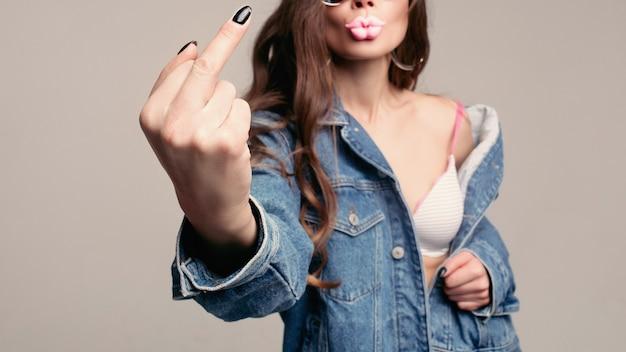 Agressieve meisje in stijlvolle zonnebril met roze dikke lippen tonen fuck op camera.