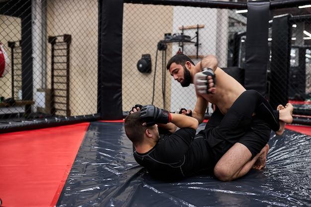 Agressieve mma-jager die tegenstander op de vloer op de mat in de sportschool slaat, tijdens gevecht zonder regels. mma-concept, shirtloze man zit op tegenstandersponsen