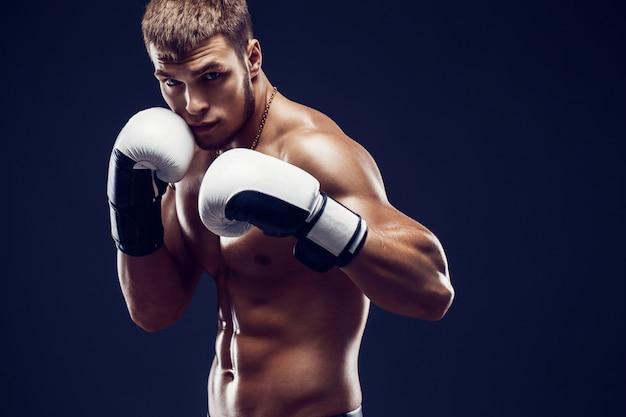 Agressieve shirtless bokser op grijze achtergrond.