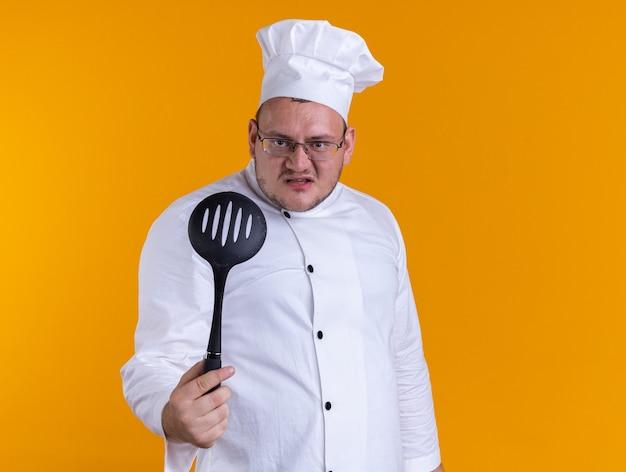 Agressieve volwassen mannelijke kok met een uniform van de chef-kok en een bril die naar de voorkant kijkt en een lepel met sleuven naar voren uitstrekt, geïsoleerd op een oranje muur met kopieerruimte