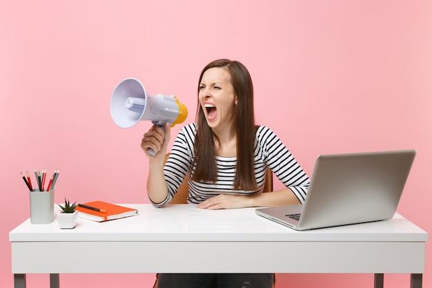 Agressieve vrouw schreeuwen in megafoon terwijl zitten en werken aan project op kantoor met pc-laptop geïsoleerd op pastel roze achtergrond. prestatie zakelijke carrière concept. kopieer ruimte voor advertentie.