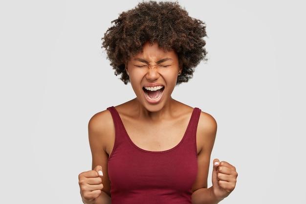 Agressieve zwarte vrouw met afro-kapsel, balt boos vuisten, voelt zich boos en wanhopig, houdt de handen voor zich vast, klaar voor strijd of uitdaging