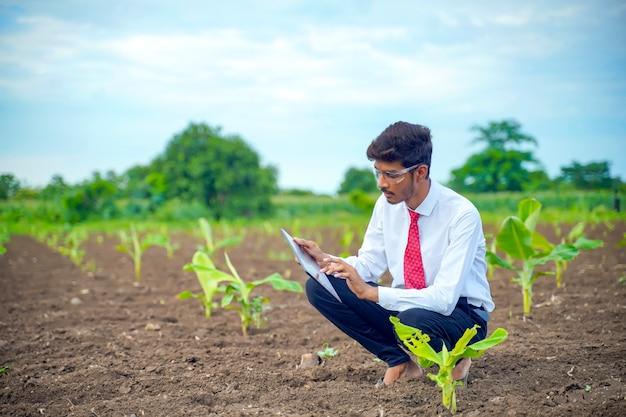 Agronoom bij een klein bananenveld, met wat informatie op het tabblad