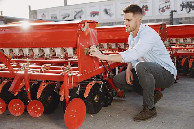 Agronoom die een nieuwe planter kiest. man op het buitenterrein van de winkel. landbouwmachines.