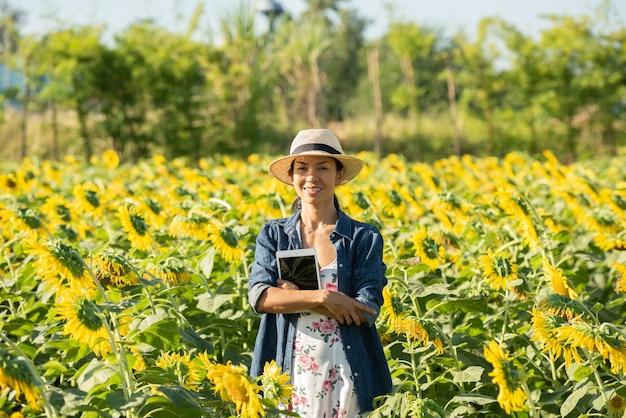 Agronoom met een tablet in zijn handen werkt in het veld met zonnebloemen. online verkopen. het meisje werkt in het veld en doet de analyse van de groei van plantencultuur. moderne technologie. landbouwconcept.