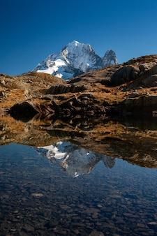 Aiguille verte van het mont blanc-massief dat water in chamonix, frankrijk overdenkt
