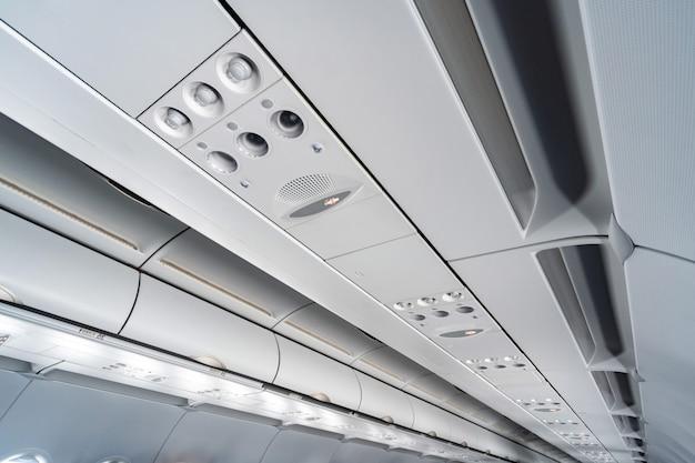 Airco bedieningspaneel over stoelen. verstopte lucht in vliegtuigcabine met mensen. nieuwe goedkope luchtvaartmaatschappij
