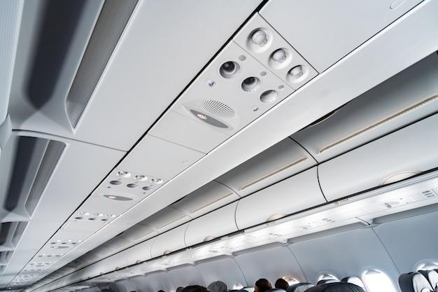 Airco-bedieningspaneel over stoelen. verstopte lucht in vliegtuigcabine met mensen. nieuwe goedkope luchtvaartmaatschappij.