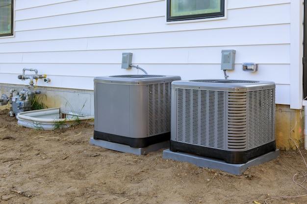 Airco-reparatiesysteemmodel is een echte elektricien op een compressor die de airconditioner bijtankt met freon