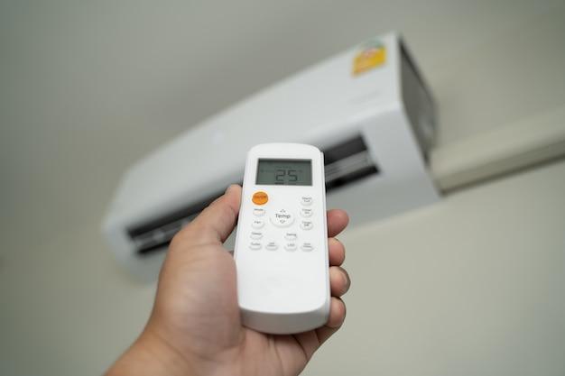 Airconditioner binnen boven de kamer man bediening afstandsbediening open airconditioner energiebesparing