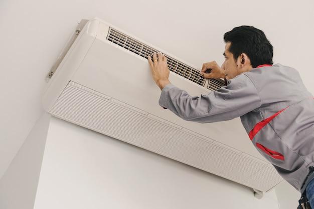 Airconditioner-reparateurs controleren en repareren lucht aan de muur.