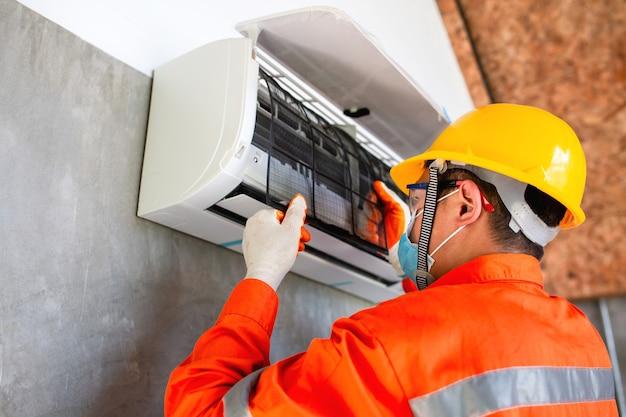 Airconditioner technicus monteur draagt masker en helm om ziekte te voorkomen, covid 19 momenteel om stoffilter voor airconditioner te installeren.