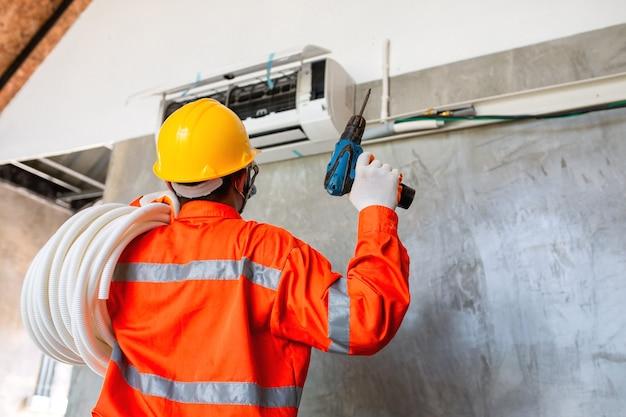 Airconditionermonteur monteur met masker en helm om ziekte te voorkomen, covid 19 gebruikt momenteel een elektrische boormachine om de airconditioner te installeren.