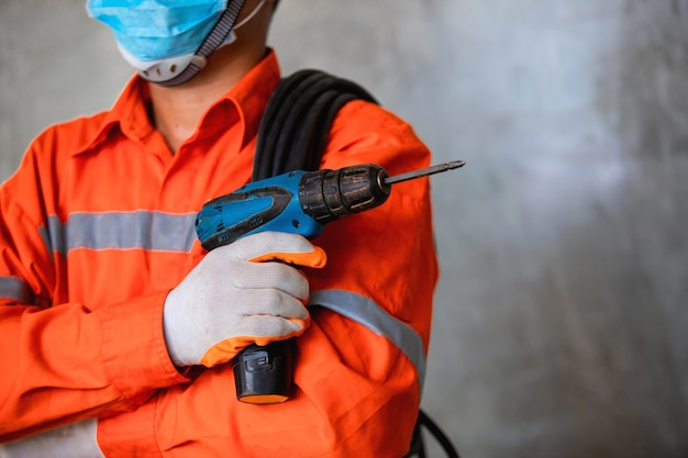 Airconditionertechnicus monteur draagt masker om ziekte te voorkomen, covid 19 houdt momenteel een elektrische boor vast om de airconditioner te installeren.