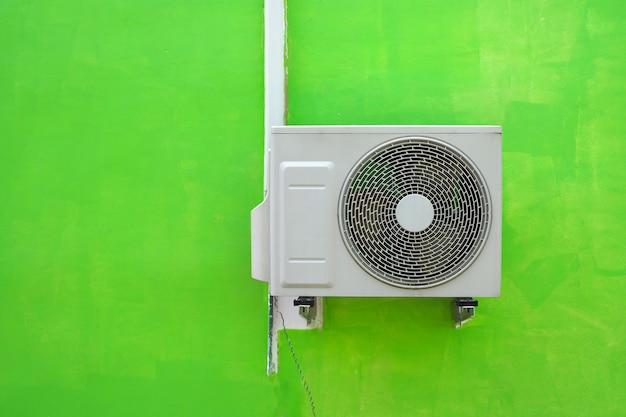 Airconditioningcompressor dichtbij de groene achtergrond van de muurtextuur