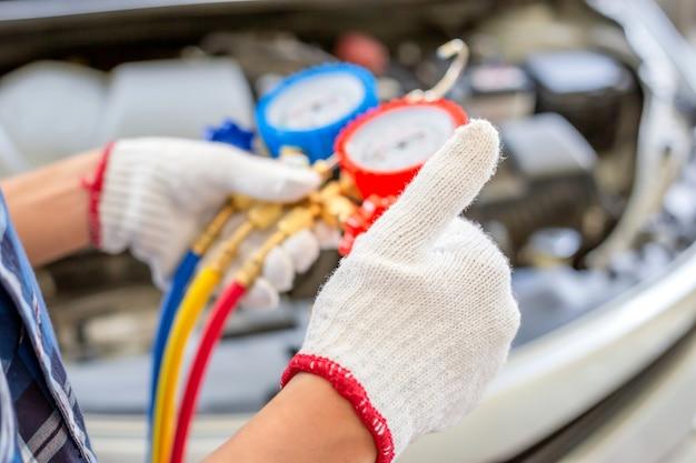 Airconditioningreparatie, reparateur die duimen omhoog geeft en monitortool vasthoudt om het auto-airconditionersysteem te controleren en te repareren, monteur controleert het koelmiddel van het auto-airconditioningsysteem