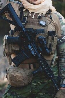 Airsoft militaire spelspeler in camouflage-uniform met gewapend aanvalsgeweer.